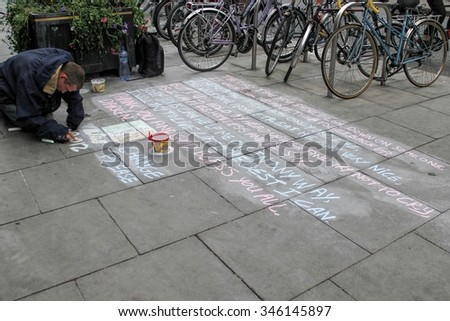 DUBLIN, IRELAND-- MAY 28, 2012: Homeless man writing a sad message on the floor, begging for small change, near to Grafton Street . - stock photo