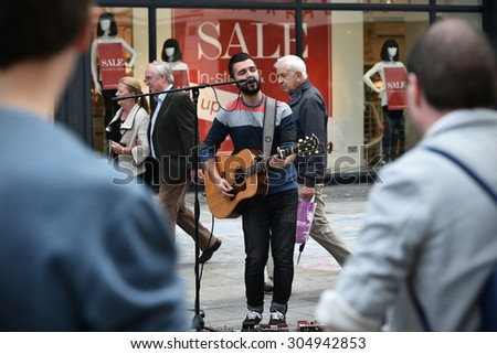 DUBLIN - JUL 22: A busker performs to a crowd on Grafton Street on Jul 22, 2015 in Dublin, Ireland. The street is a main tourist attraction in the Irish capital, famous for its lively atmosphere. - stock photo
