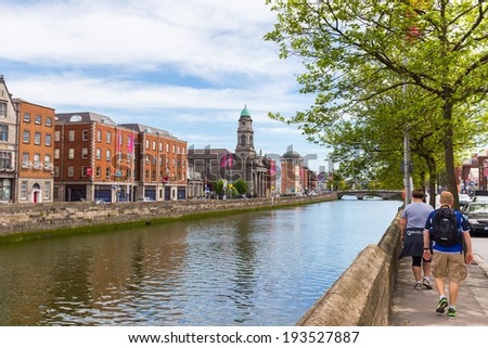 DUBLIN - MAY 17, 2014: Tourists walking alongside the River Liffey. Dublin Ireland is a popular tourist destination.  - stock photo