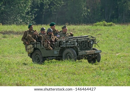 DUBOSEKOVO, RUSSIA - JULY 13: military history club members reenacting Allies recon patrol ride Willys MB jeep during Field of Battle military history festival on July 13, 2013 in Dubosekovo, Russia  - stock photo