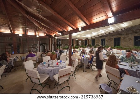 DUBROVNIK, CROATIA - MAY 27, 2014: Guests and waitress in Proto restaurant, one of Dubrovnik's best known places for fish specialities. - stock photo