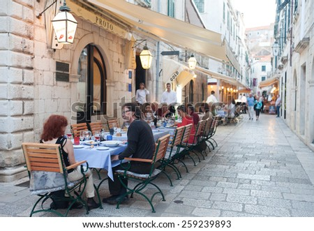 DUBROVNIK, CROATIA - MAY 28, 2014: Guests sitting at Proto restaurant terrace, one of Dubrovnik's best known places for fish specialities. - stock photo