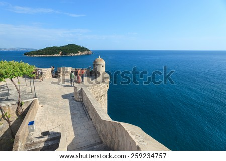 DUBROVNIK, CROATIA - MAY 26, 2014: Tourist at Old city walls with Lokrum island and Adriatic sea in background. Old wall is one of Dubrovnik's most famous feature. It is almost 2 km long. - stock photo