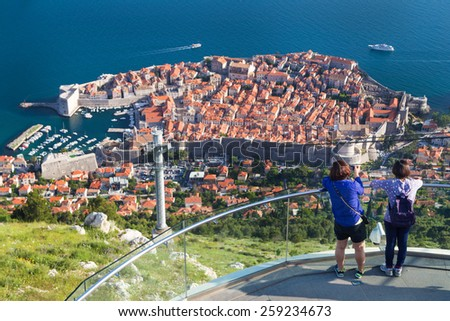 DUBROVNIK, CROATIA - MAY 26, 2014: Tourists at viewpoint at cable car station which connects Ploce and mountain Srdj above town and enjoy a panoramic view of Old Town and the surrounding islands. - stock photo