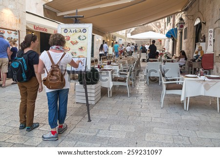 DUBROVNIK, CROATIA - MAY 28, 2014: Tourists looking at menu in front of the restaurant terrace. Dubrovnik has many restaurants which offer traditional Dalmatian cuisine and some great wine lists. - stock photo