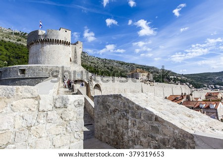 DUBROVNIK, CROATIA - OCT 25, 2015: Tourists walking on the Ancient walls of old town Dubrovnik, Croatia. Background is the highest point Minceta Tower on the castle. - stock photo