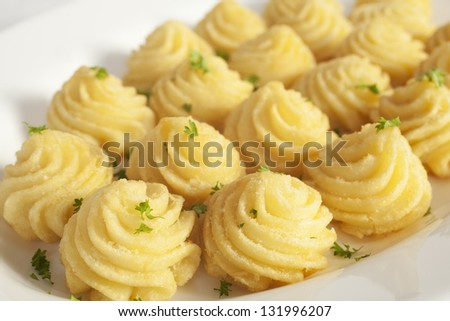 Duchess potatoes, mashed potato mixed with egg, piped into swirls and baked in the oven. - stock photo