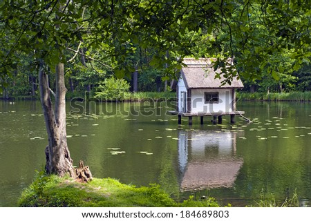 Duck house on a lake in a park - stock photo