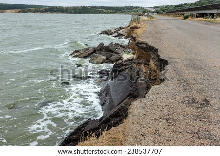 Due to violations of technology in the construction of roads, water, more rain and huge waves of the sea during a storm split and broke and washed away the asphalt road and formed a landslide failure - stock photo