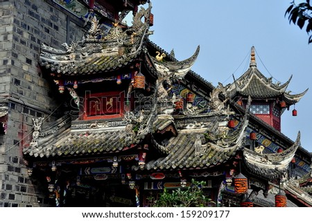 DUJIANGYAN, CHINA:  The Ming Dynasty Lang Qiao covered bridge over the Min River with its opulent carved dragons and flying eaved roofs * - stock photo