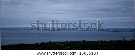 Duluth Harbor before dawn breaks as two ships head toward port. - stock photo