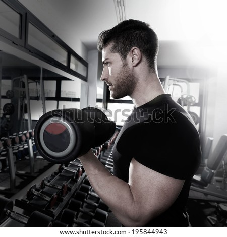 Dumbbell man at gym workout biceps fitness weightlifting - stock photo