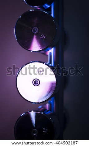 Dumbbell weights on dumbells rack in fitness gym for weight training, bodybuilding and sports strength training. - stock photo