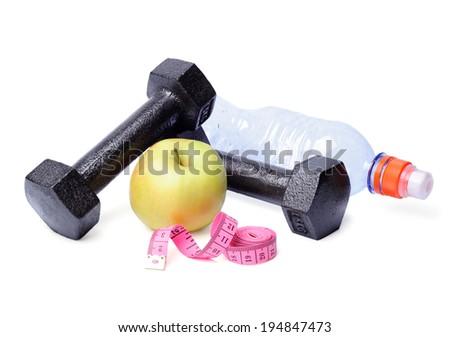Dumbbells, apples, centimeter and bottle isolated on white background - stock photo