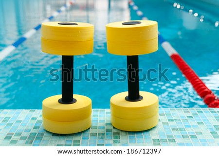 Dumbbells for Aqua Aerobics inthe pool - stock photo