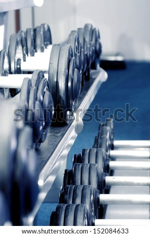 Dumbbells in a rack at the gym. - stock photo