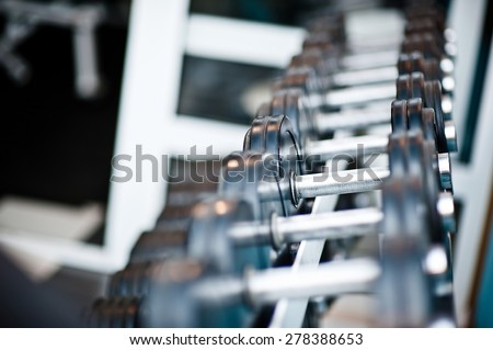 Dumbbells in the gym in modern sports club. Weight training equipment - stock photo