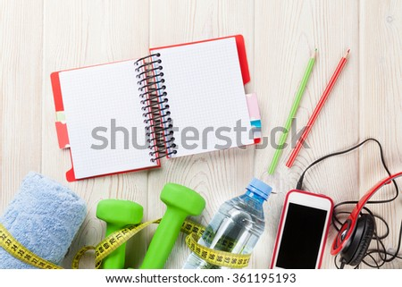 Dumbbells, water bottle, smartphone, headphones and notepad. Fitness concept. Top view with copy space - stock photo