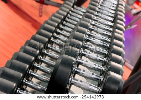 Dumbbells weights lined up in a fitness studio - stock photo