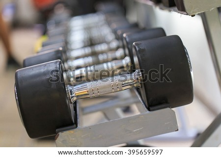 Dumbells for fitness in a rack at the gym - stock photo