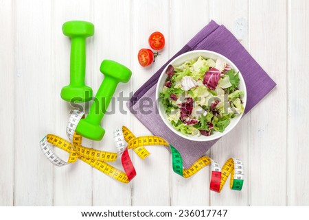 Dumbells, tape measure and healthy food. Fitness and health - stock photo