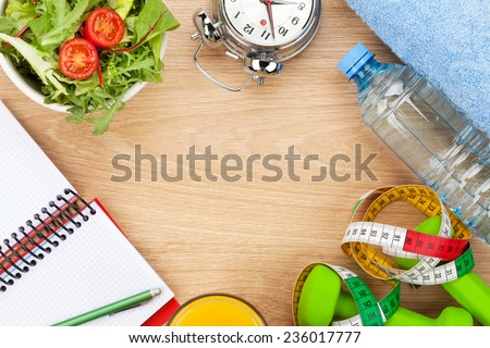 Dumbells, tape measure and healthy food over wooden background. Fitness and health. View from above with copy space - stock photo