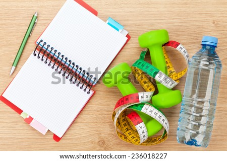Dumbells, tape measure and notepad for copy space. Fitness and health. Isolated on white background - stock photo