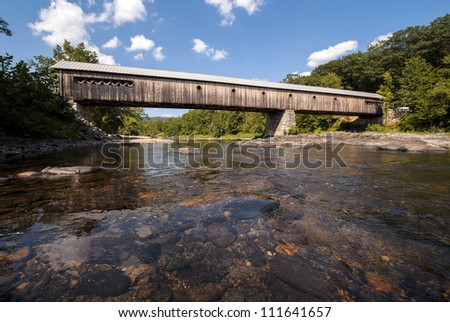 Dummerston covered bridge in southern vermont with a fresh water stream flowing under it.  Built in 1872 its one of Vermont's longest covered bridges still used today. - stock photo