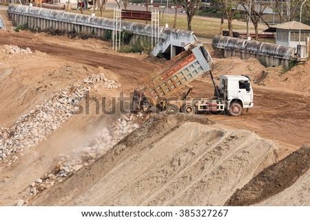 Dump truck dumping rock in construction site. - stock photo