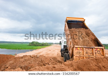 Dump truck unloading soil or sand at construction site during road works - stock photo