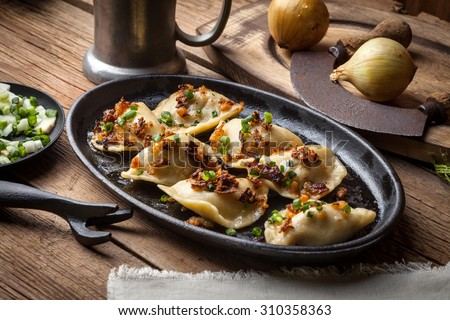 Dumplings with meat, onions and bacon on a cast iron skillet. Selective focus. - stock photo