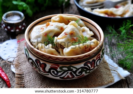 Dumplings with potatoes and mushrooms with fried onions in a traditional ceramic plate on a wooden table. Ukrainian traditional cuisine. rustic style. selective focus - stock photo