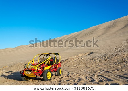 Dune buggy at the foot of a large sand dune in Huacachina, Peru - stock photo