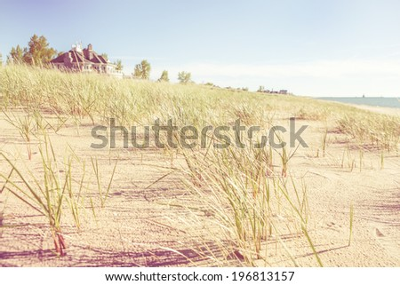 Dune grasses with beach house and lighthouse in the distance - stock photo