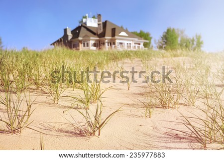 Dune grasses with beach house  in the distance - stock photo