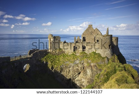 Dunluce Castle - a famous landmark from the coast of Northern Ireland - on a beautiful sunny afternoon. - stock photo