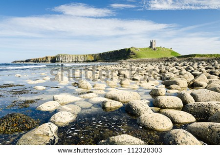 Dunstanburgh Castle / Iconic Dunstanburgh castle ruin built in the 14th century viewed from the northern rocky shoreline - stock photo