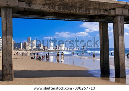 DURBAN, SOUTH AFRICA : MARCH 28, 2016: View from under Vetch's pier of many unknown people on beach and city skyline in Durban South Africa - stock photo