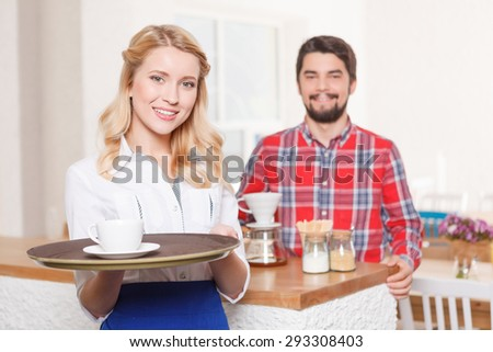 During work. Portrait of young petty blond-haired waitress standing with tray on background of satisfied customer with coffee. - stock photo