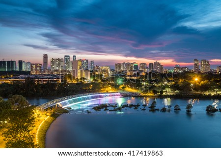 Dusk over Ban Nguyet Lake with starlight bridge by the weekend, the central  of Phu My Hung, District 7 (new urban/city area Ho Chi Minh City, Vietnam) - stock photo