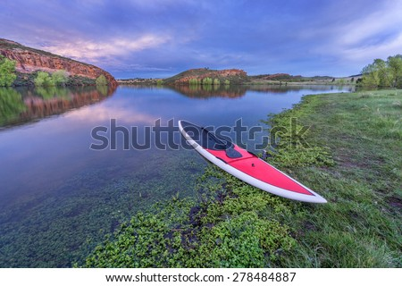dusk over calm lake with a red stand up paddleborad  with a paddle on shore - Horsetooth Reservoir, Fort Collins, Colorado - stock photo