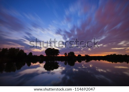 Dusk sky over the lake - stock photo