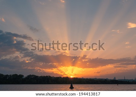 Dusk sun rays over the river. Sunset landscape. - stock photo