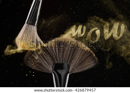 Dust English lettering. The word WOW made of shiny golden elements of powder. Qualitative cosmetics for perfect visage. Fluffy atmosphere. - stock photo