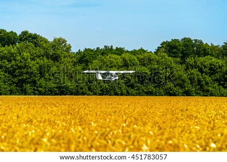 Duster, small old plane for agricultural spraying, flying above the wheat field - stock photo