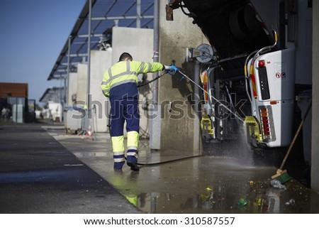 Dustman cleaning a Lorry Bin - stock photo