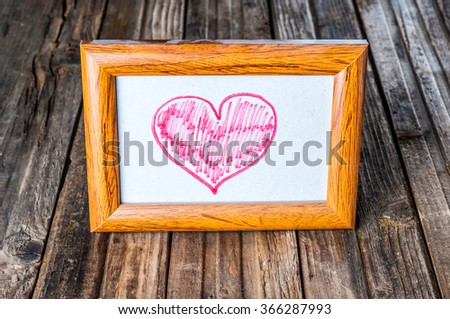 Dusty photo frame with drawing heart on wooden background - stock photo
