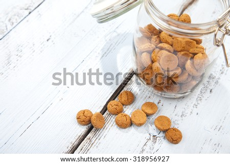 Dutch candy pepernoot with glass jar and white wooden background - stock photo