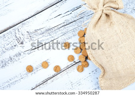 Dutch candy pepernoot with jute bag on white blue wooden background - stock photo