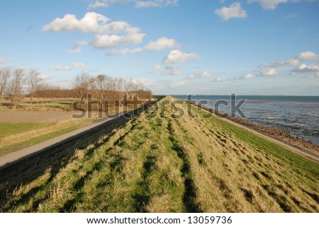 Dutch dike protecting land against the sea during calm ebb tide. Place: Kats Oosterschelde Zealand - stock photo